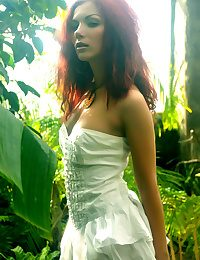 A redhead nymph slowly strips off her dainty dress, revealing a composed fair complexion and gorgeous bod that stands out from the lush, green surroundings.